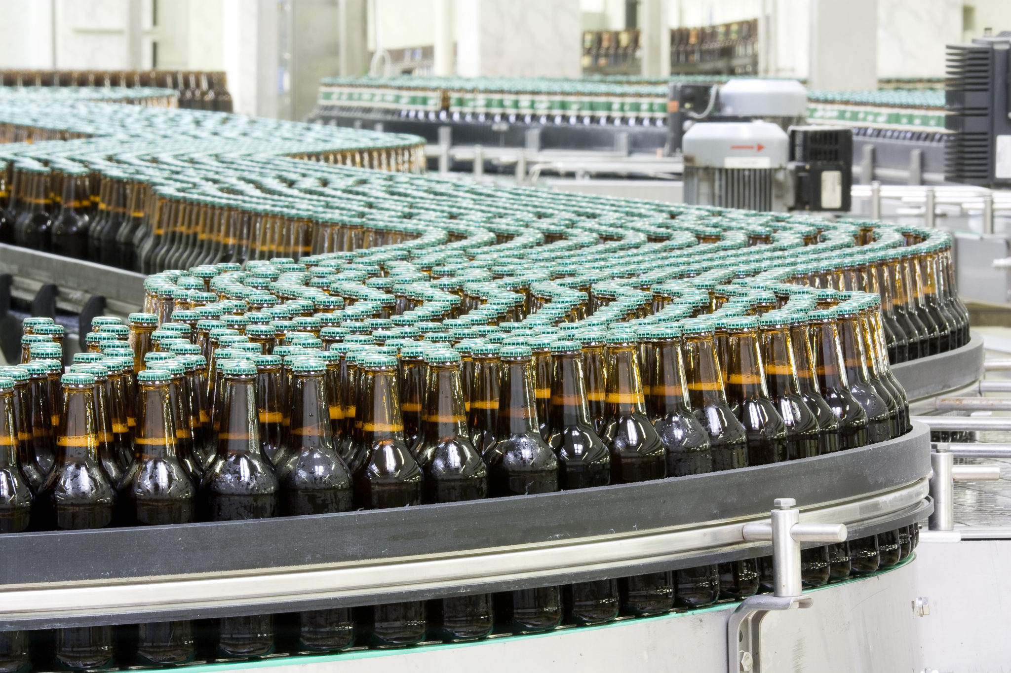 Kaman Automation iStock 000014051172 Full Bottles of beer on conveyor in brewery scaled